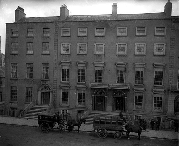 """The photo, """"Imperial Hotel and coaches, The Mall, Waterford,"""" shows two horse-drawn cabs. Photo taken between 1900 and 1910, from the National Library of Ireland."""